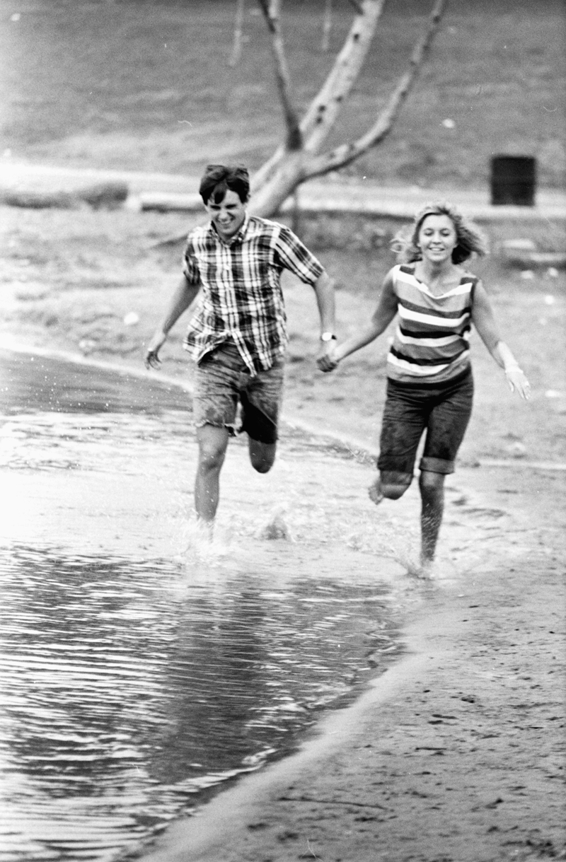 Couple running along the beach at the 1965 Mariposa Folk Festival in Calendon. Image no. ASC02124.