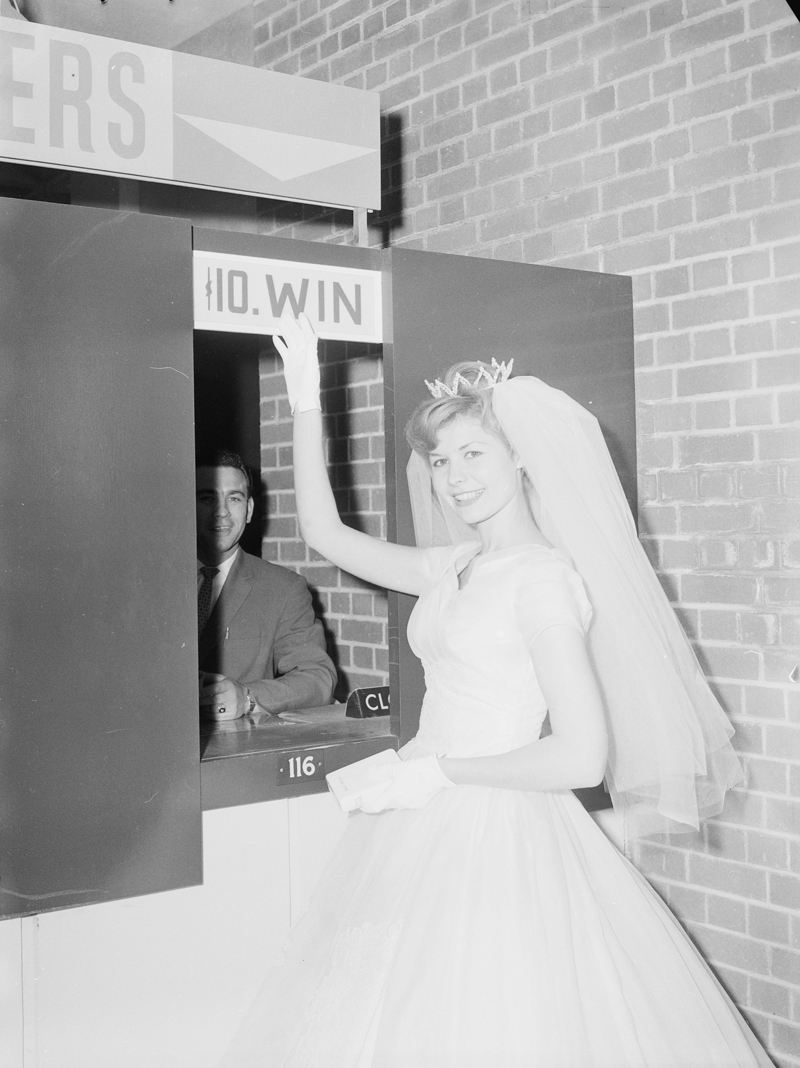 "Woman in wedding dress and veil standing at ""$10 win"" window at Old Woodbine Racetrack, 1960. Image no. ASC03688."