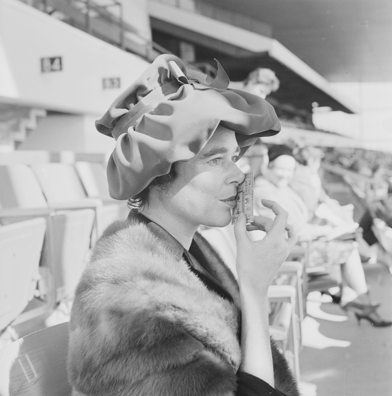 Woman kissing a ticket at the Woodbine Racetrack, 1960. Image no. ASC03814.