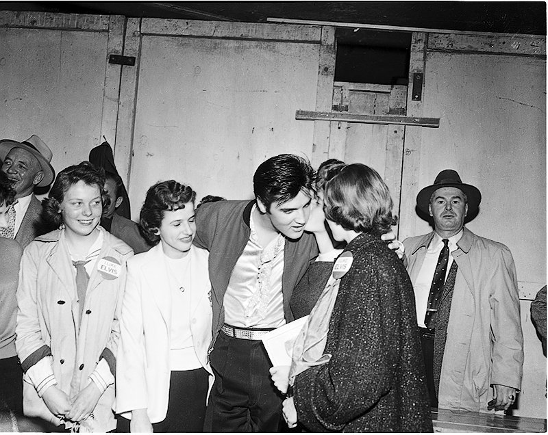 Elvis standing with group of female fans; some of the fans are wearing badges, Elvis has tilted his head to get a kiss on the cheek from one of the fans. Image no. ASC00846.